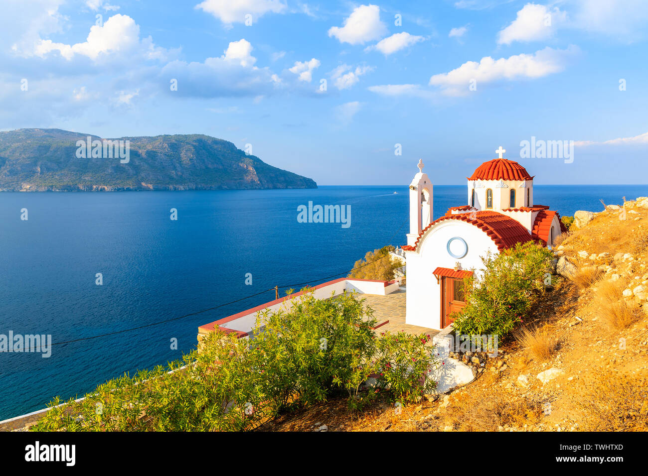 White church on high cliff above sea near Karpathos port, Karpathos island, Greece Stock Photo