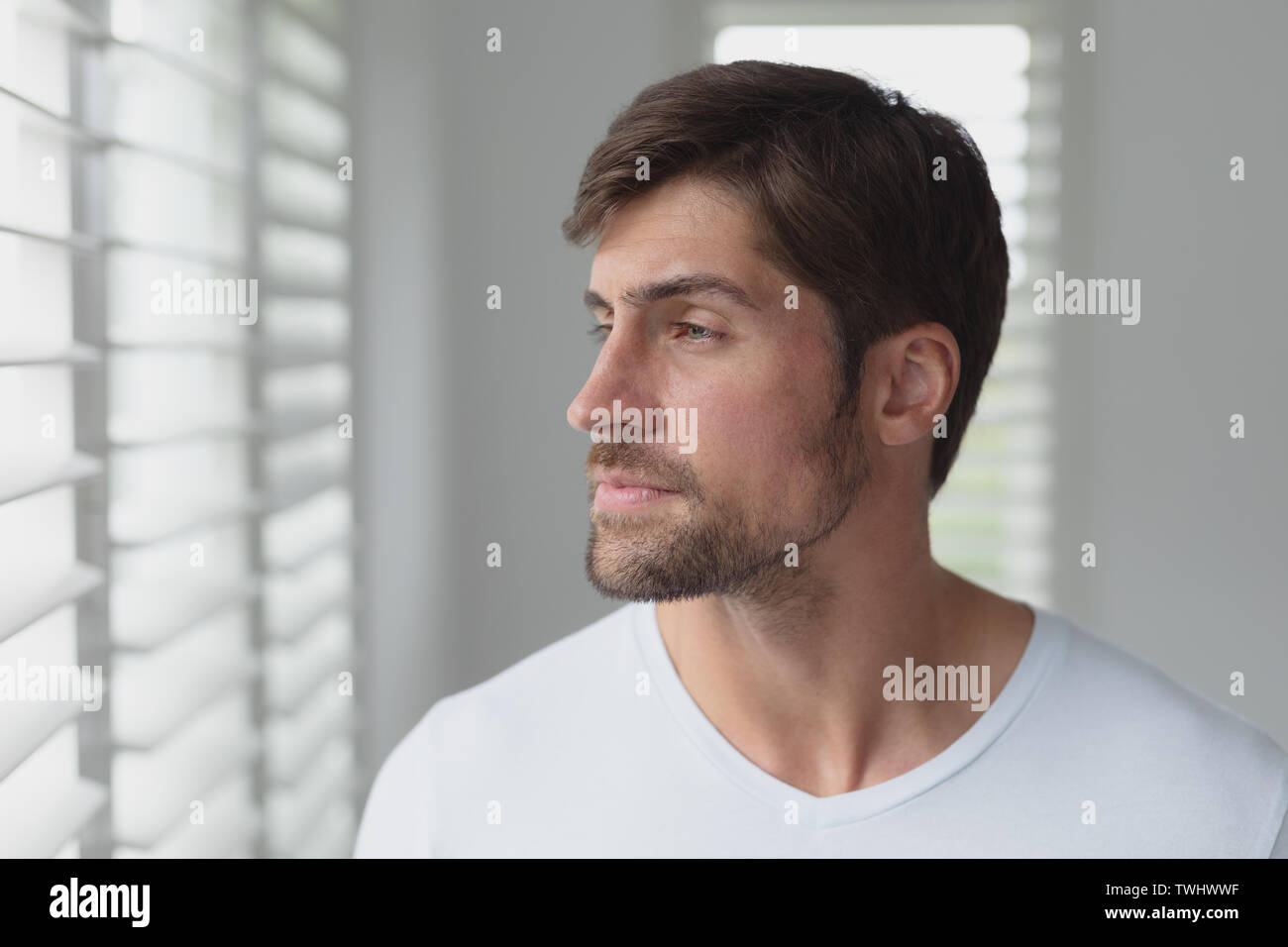 Side view of thoughtful Caucasian man looking through window blind at home - Stock Image