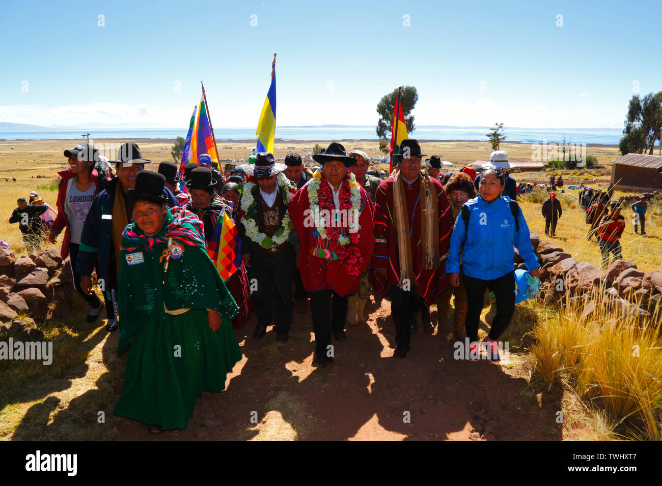Bolivia 20th June 2019: Bolivian president Evo Morales Ayma (centre) leads an International Hike along a section of the Qhapaq Ñan Inca road from Azafranal near Lake Titicaca (which is visible in the background). The event was organised by the Ministry of Cultures & Tourism to promote tourism and Bolivia's indigenous cultures. - Stock Image
