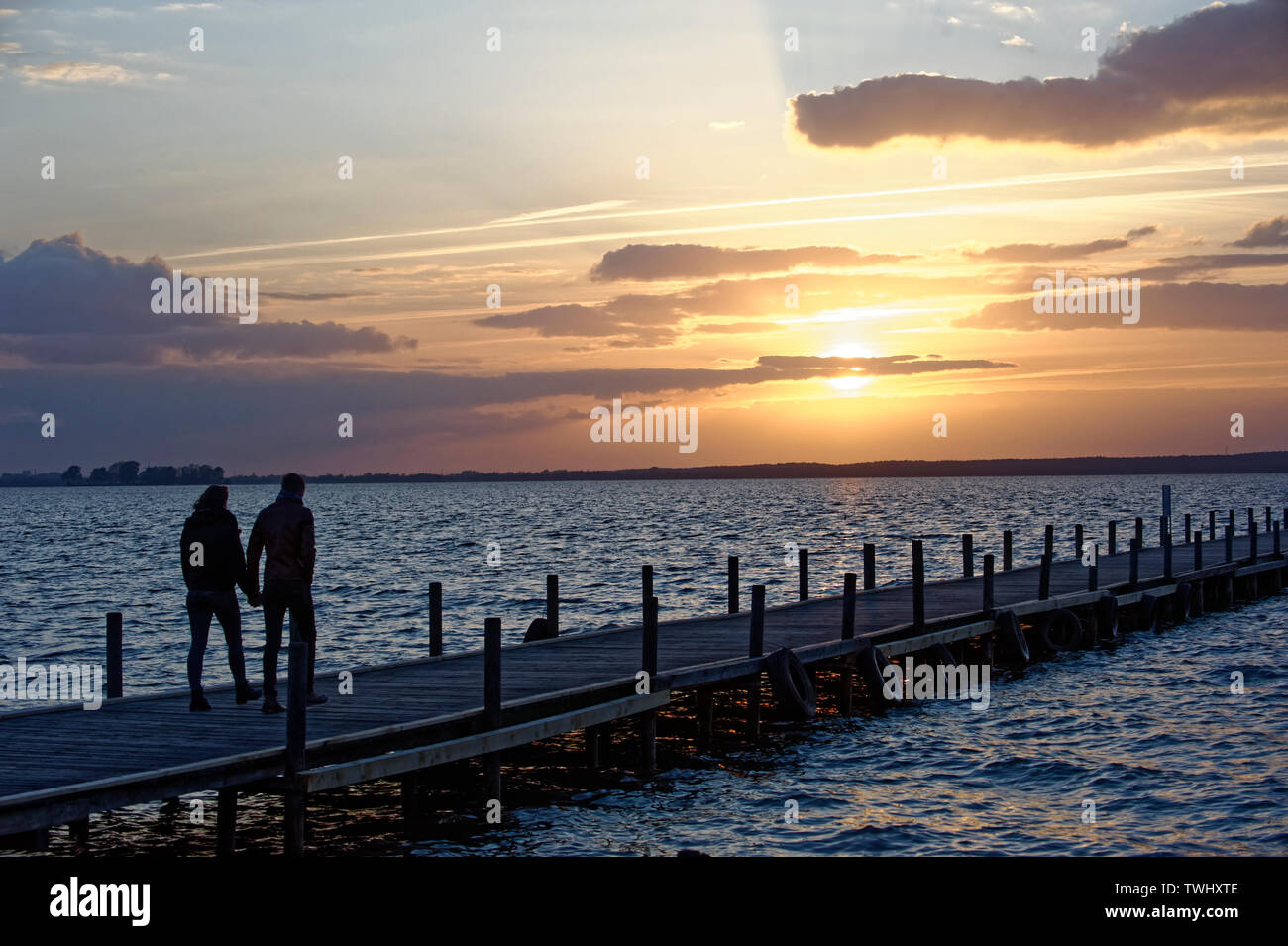 Young couple walking on wooden pier above lake at sunrise.Steinhuder Meer,Germany. - Stock Image