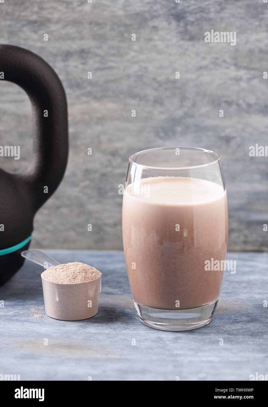 Glass Of Chocolate Protein Shake With Milk And Banana Whey Protein In Scoop And Black Sporting Kettlebell In Background Stock Photo Alamy