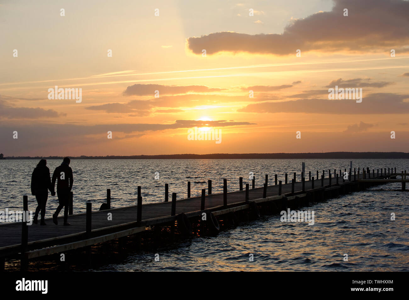 Young couple walking on wooden pier above lake at sunrise. - Stock Image