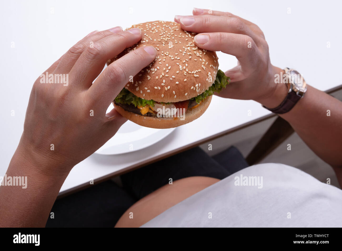 An Overhead View Of An Overweight Woman Holding Hamburger In Hand - Stock Image