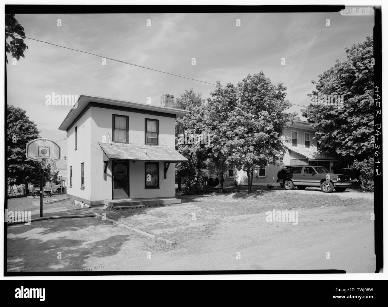 SINGLE-FAMILY HOUSES, FORMERLY OCCUPIED BY LOWER-LEVEL MANAGERS, ON 2ND STREET, LOOKING WEST; THESE ARE AMONG THE FEW CONCRETE-CONSTRUCTED DWELLINGS OF THEIR TYPE IN SOUTHWESTERN PENNSYLVANIA'S COAL TOWNS - Town of Cairnbrook, Cairnbrook, Somerset County, PA; Pitcairn, John; Loyal Hanna Coal and Coke Company; Madrid, transmitter - Stock Image