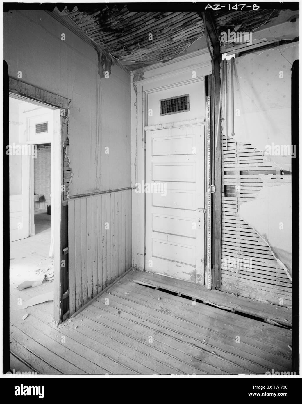 Several of the rental rooms are joined by doors, and each room is accessed from the corridor. Originally, the transoms were glazed. When a central heating-cooling system was installed, the transoms were modified to accommodate air grilles that are supplied by a duct located in the corridor. The five-panel door and wood wainscot are original features. However, the wainscot does not occur in every room. The lath and plaster partitions and the wood flooring are typical of the original construction. Credit GADA-MRM. - Stroud Building, 31-33 North Central Avenue, Phoenix, Maricopa County, AZ - Stock Image
