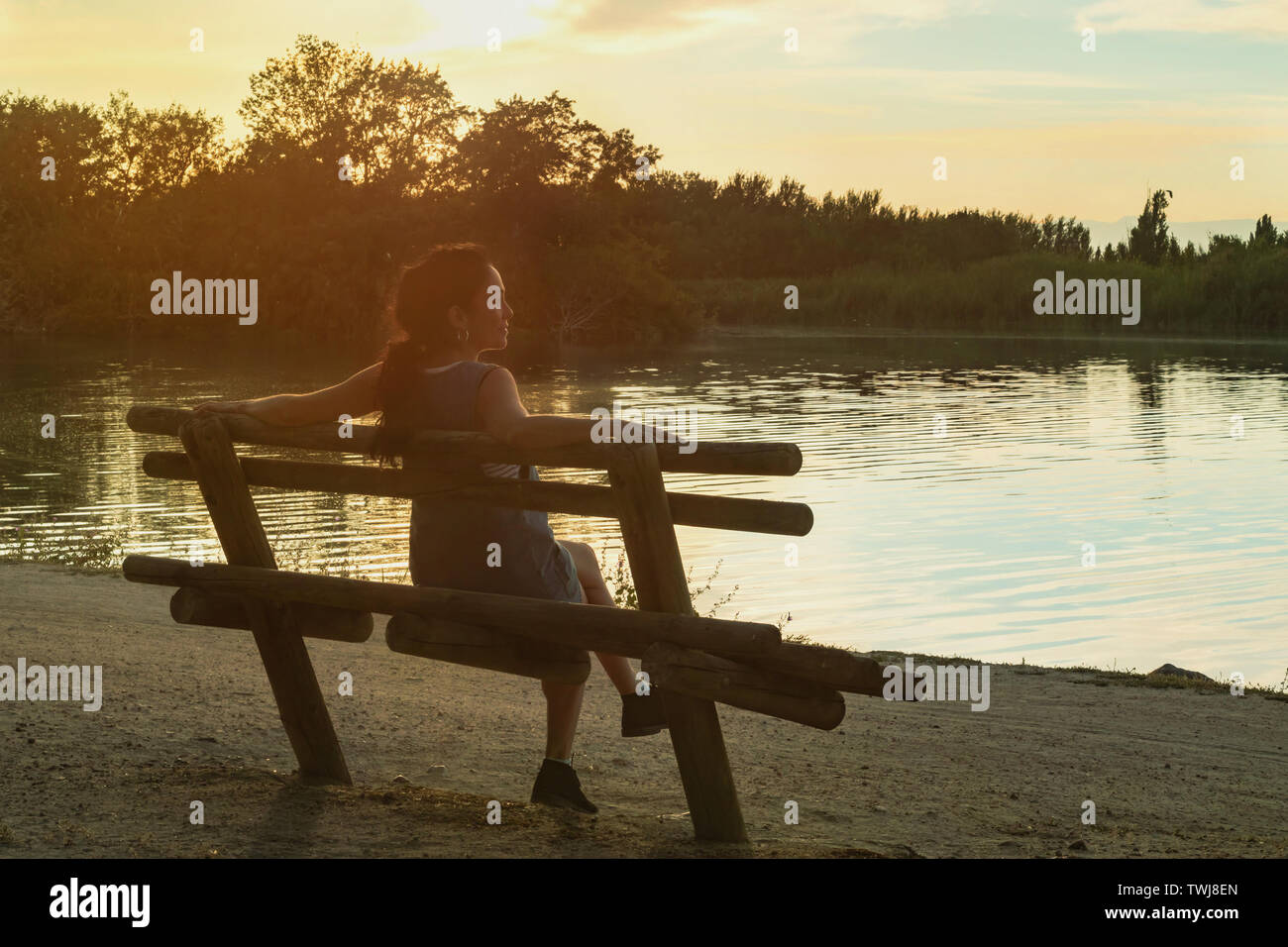 Young brunette woman watching the sunset, sitting on a wooden bench in front of a Tajo river, Spain Stock Photo
