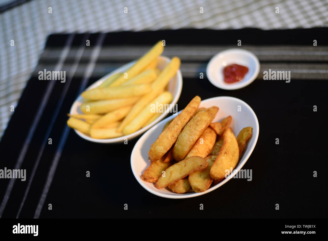 Crispy potato chips and wedges, setup nicely on table ready to serve - Stock Image