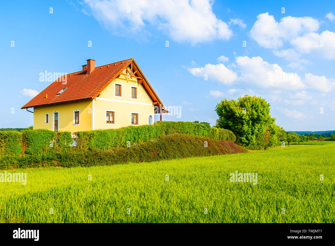 Yellow traditional house with red tile roof on green meadow in spring landscape of Burgerland in Strem village, Austria Stock Photo