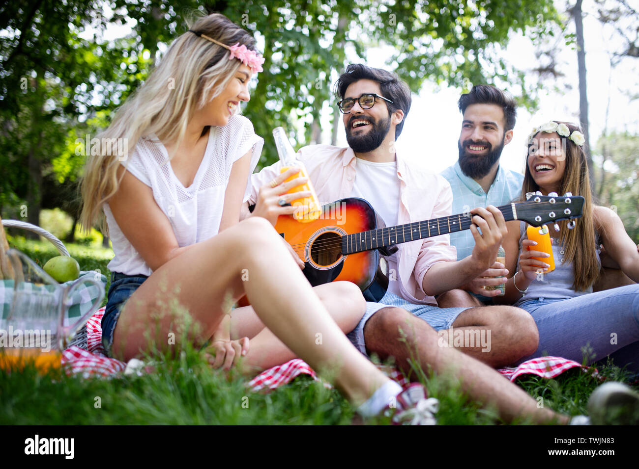 Happy young friends having picnic in the park - Stock Image