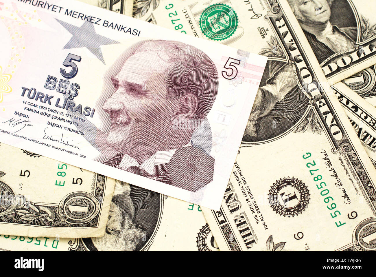 A close up image of a purple five Turkish lira bank note on a background of American one dollar bills in macro Stock Photo