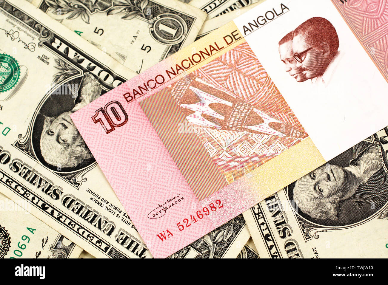 An red and white ten Angolan kwanza bank note on a background of American one dollar bills Stock Photo