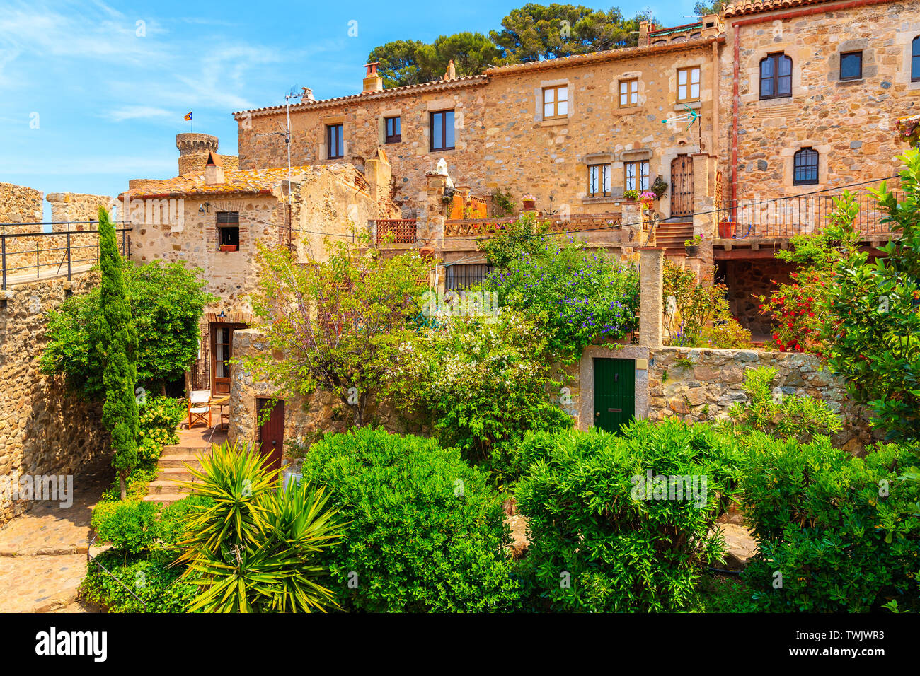 Green tropical plants and stone houses in old town of Tossa de Mar, Costa Brava, Spain Stock Photo