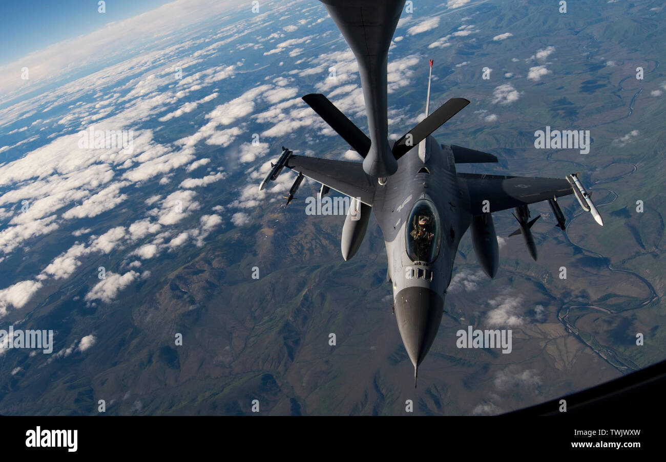 A U.S. Air Force F-16 Fighting Falcon pilot from the 13th Fighter Squadron, Misawa Air Base, Japan, approaches to receive fuel from a KC-135 Stratotanker during RED FLAG-Alaska 19-2 near Eielson Air Force Base, Alaska, June 18, 2019. RF-A is an annual U.S. Pacific Air Forces field training exercise for U.S. and international partners to enhance combat readiness of participating forces. The KC-135 is assigned to the 909th Air Refueling Squadron, Kadena Air Base, Japan. RF-A is an annual U.S. Pacific Air Forces field training exercise for U.S. and international partners to enhance combat readine - Stock Image