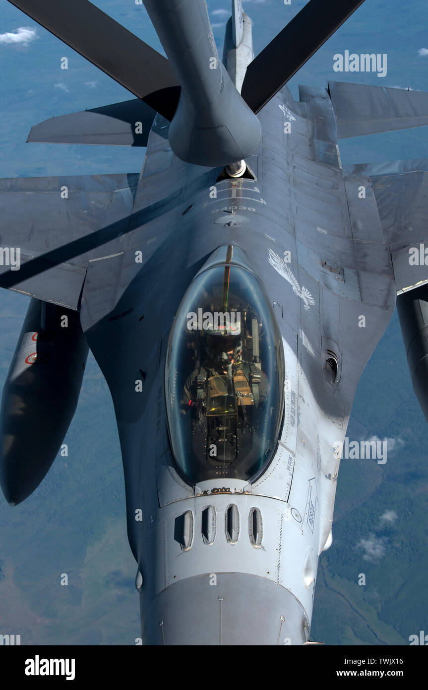 A U.S. Air Force F-16 Fighting Falcon pilot from the 13th Fighter Squadron, Misawa Air Base, Japan, receives fuel from a KC-135 Stratotanker during RED FLAG-Alaska 19-2 near Eielson Air Force Base, Alaska, June 18, 2019. The 13th FS is one of various units, to include NATO partners, participating in exercise RF-A. The KC-135 is assigned to the 909th Air Refueling Squadron, Kadena Air Base, Japan. RF-A is an annual U.S. Pacific Air Forces field training exercise for U.S. and international partners to enhance combat readiness of participating forces. Airmen from Misawa and Kadena Air Base joined - Stock Image