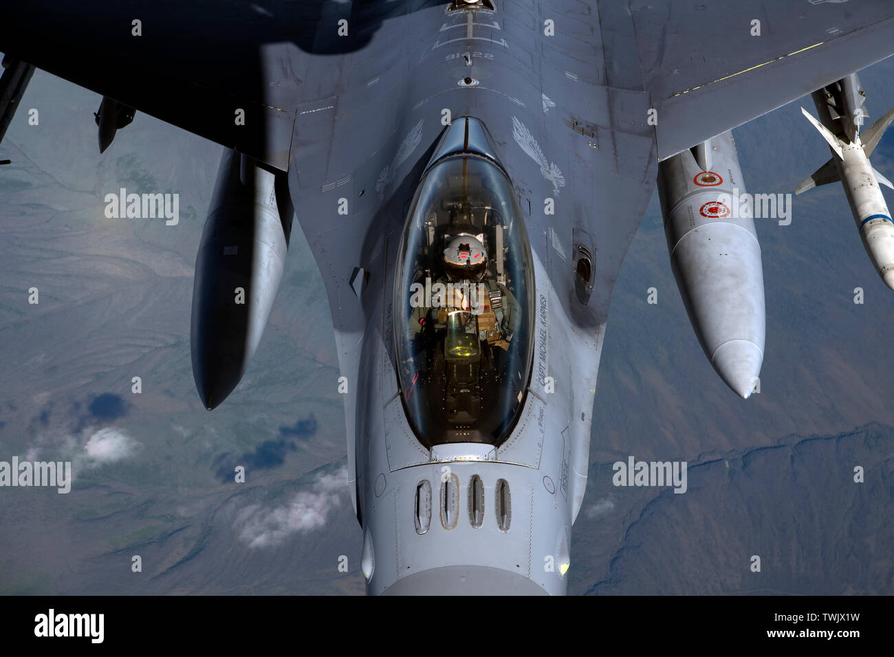 A U.S. Air Force F-16 Fighting Falcon pilot from the 13th Fighter Squadron, Misawa Air Base, Japan, receives fuel from a KC-135 Stratotanker during RED FLAG-Alaska 19-2 near Eielson Air Force Base, Alaska, June 18, 2019. RF-A is an annual U.S. Pacific Air Forces field training exercise for U.S. and international partners to enhance combat readiness of participating forces. The KC-135 is assigned to the 909th Air Refueling Squadron, Kadena Air Base, Japan. Airmen from Misawa and Kadena Air Base joined more than 2000 participants for the Pacific Air Forces-sponsored exercise, which aims to impro - Stock Image