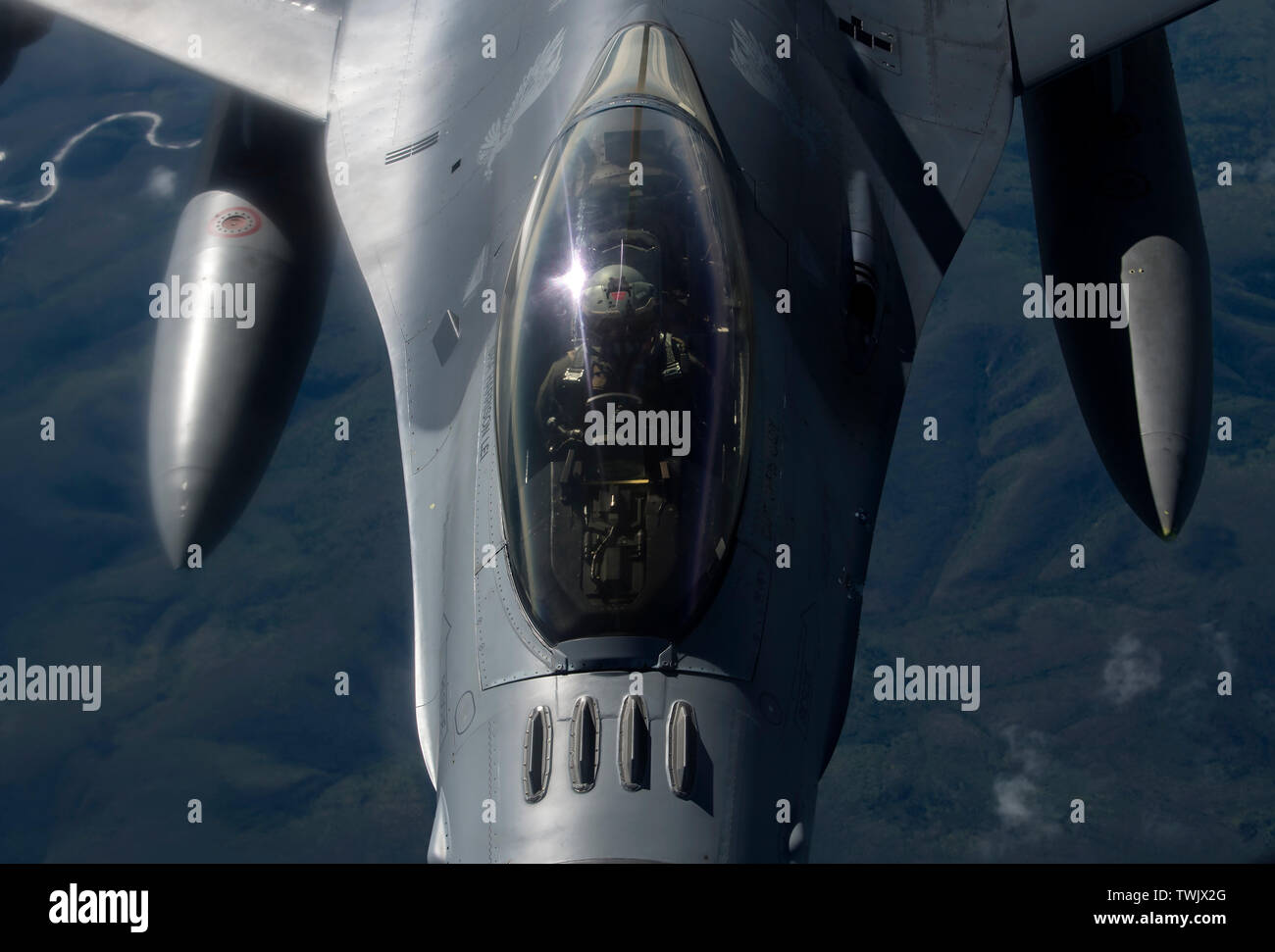 A U.S. Air Force F-16 Fighting Falcon pilot from the 13th Fighter Squadron, Misawa Air Base, Japan, receives fuel from a KC-135 Stratotanker during RED FLAG-Alaska 19-2 near Eielson Air Force Base, Alaska, June 18, 2019. The 13th FS is one of various units, to include NATO partners, participating in exercise RF-A. The KC-135 is assigned to the 909th Air Refueling Squadron, Kadena Air Base, Japan. Airmen from Misawa and Kadena Air Base joined more than 2000 participants for the Pacific Air Forces-sponsored exercise, which aims to improve interoperability between U.S. and international partners. - Stock Image