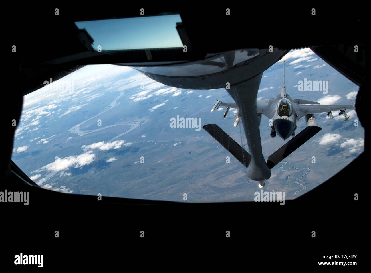 A U.S. Air Force F-16 Fighting Falcon pilot from the 13th Fighter Squadron, Misawa Air Base, Japan, approaches to receive fuel from a KC-135 Stratotanker during RED FLAG-Alaska 19-2 near Eielson Air Force Base, Alaska, June 18, 2019. The 13th FS is one of various units, to include NATO partners, participating in exercise RF-A. The KC-135 is assigned to the 909th Air Refueling Squadron, Kadena Air Base, Japan. Airmen from Misawa and Kadena Air Base joined more than 2000 participants for the Pacific Air Forces-sponsored exercise, which aims to improve interoperability between U.S. and internatio - Stock Image
