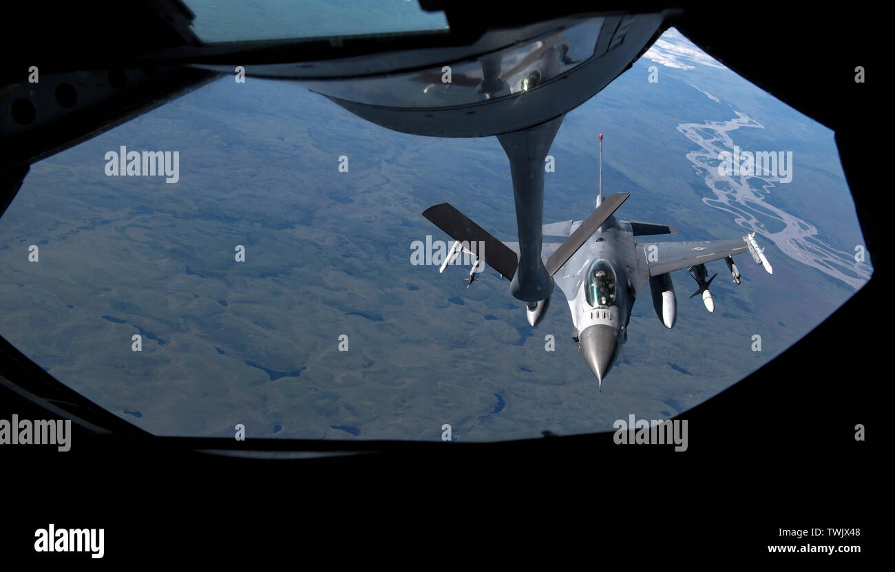A U.S. Air Force F-16 Fighting Falcon pilot from the 13th Fighter Squadron, Misawa Air Base, Japan, approaches to receive fuel from a KC-135 Stratotanker, assigned to the 909th Air Refueling Squadron, Kadena Air Base, Japan. during RED FLAG-Alaska 19-2 near Eielson Air Force Base, Alaska, June 18, 2019. The 13th FS is one of various units, to include NATO partners, participating in exercise RF-A. The Pacific Air Forces-sponsored exercise takes place in the Joint Pacific Alaska Range Complex, which provides a realistic training environment with approximately 67,000 square miles of airspace. (U. - Stock Image