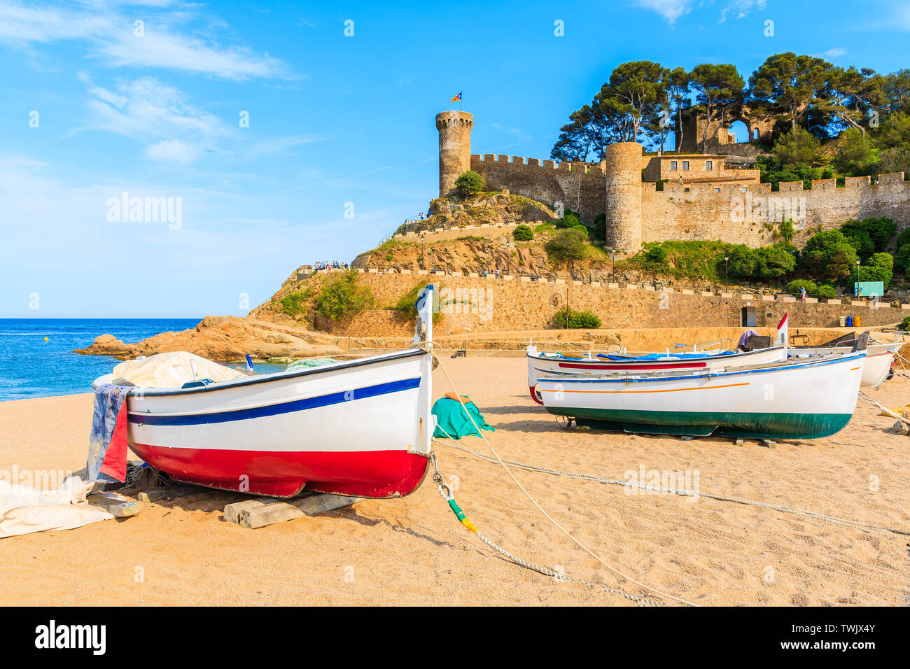 Fishing boats on golden sand beach in bay with castle in background, Tossa de Mar, Costa Brava, Spain Stock Photo