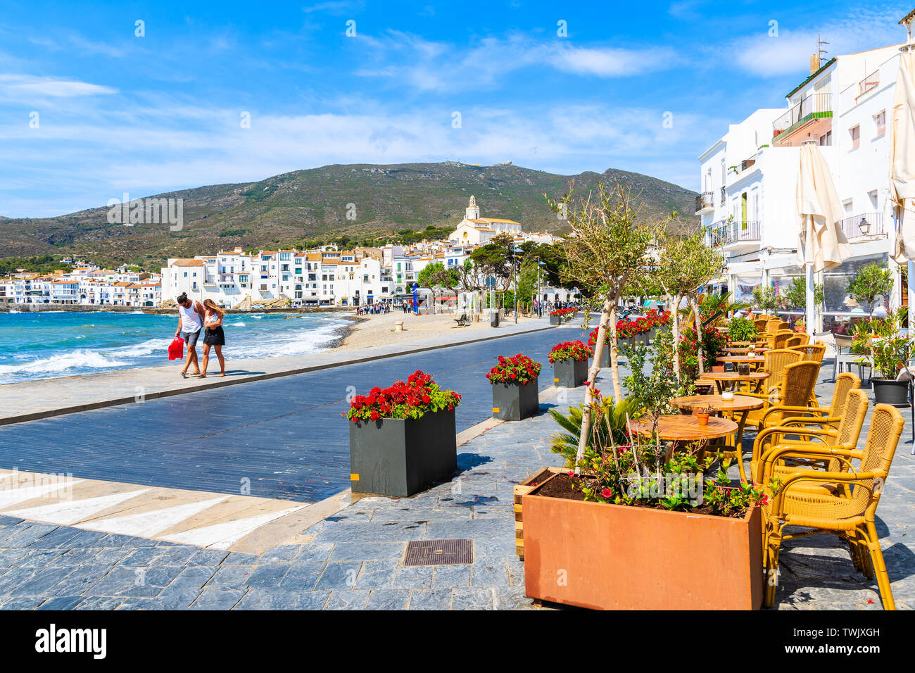Unidentified young couple walking along beach in Cadaques white village, Costa Brava, Spain Stock Photo