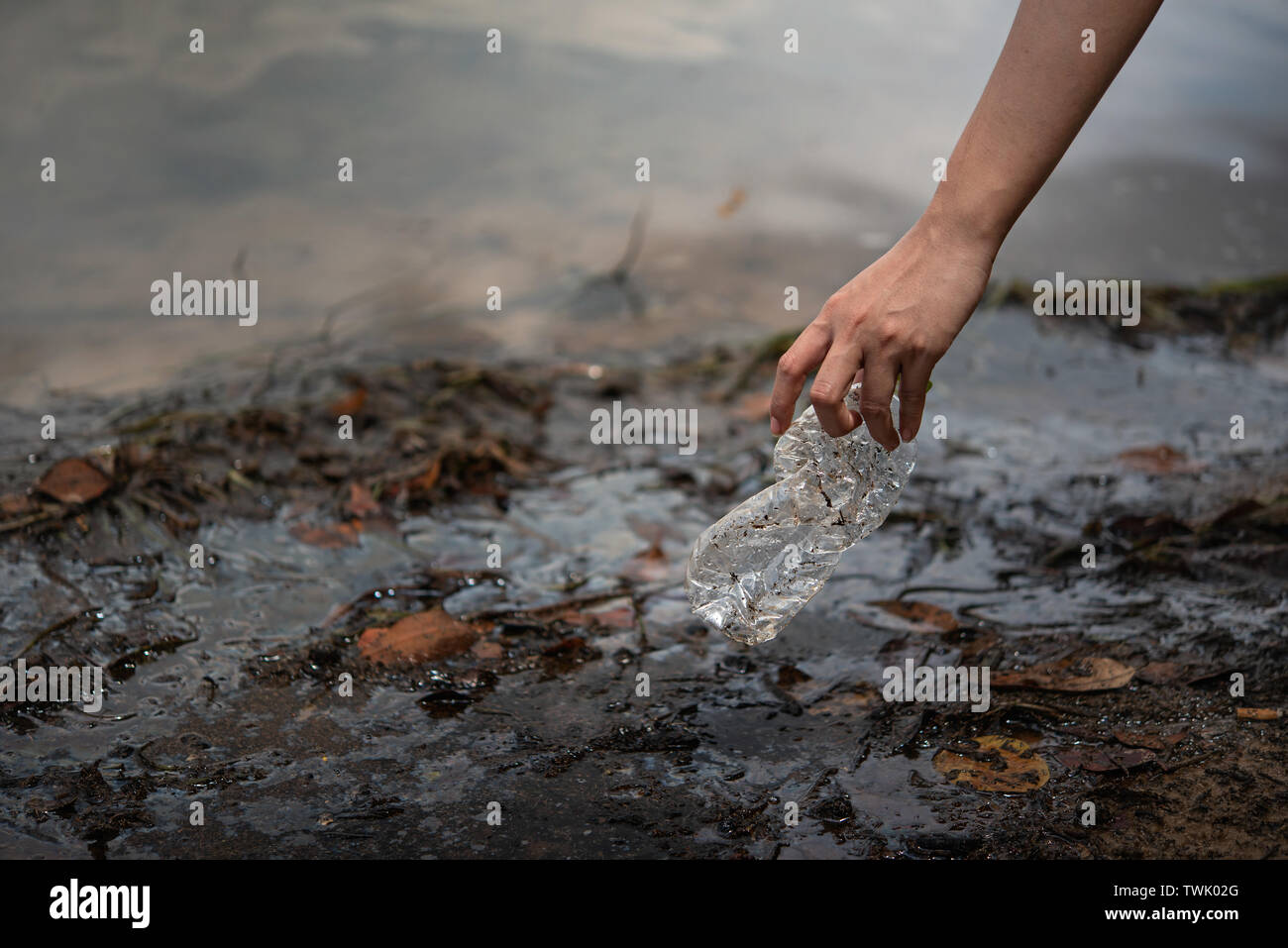 hand pick up plastic bottle from water. save environment and beat plastic pollution , Selective focus - Stock Image