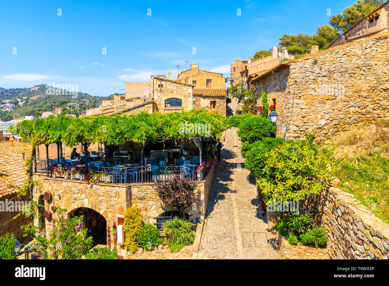 Narrow street with stone houses in old town in Tossa de Mar, Costa Brava, Spain Stock Photo