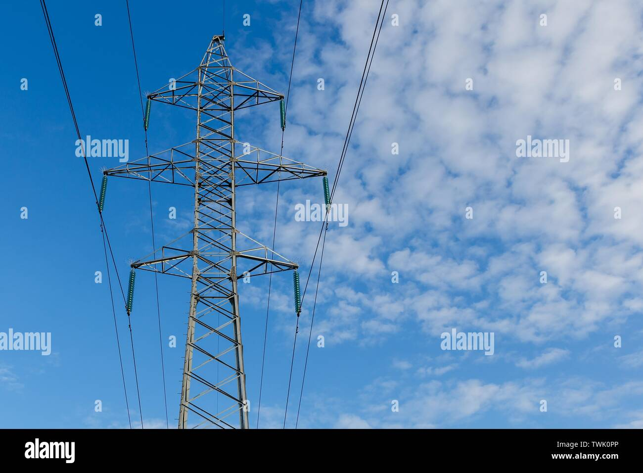 Power lines on metal pillars against a blue sky with clouds, high voltage power line - Stock Image