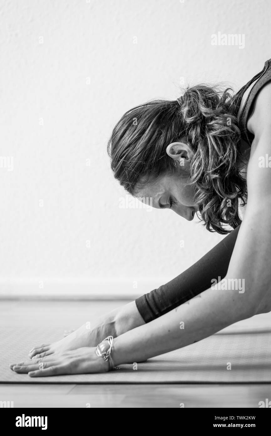 Side view of a young woman in her early 30's performing astanas or postures used in the practice of yoga. - Stock Image