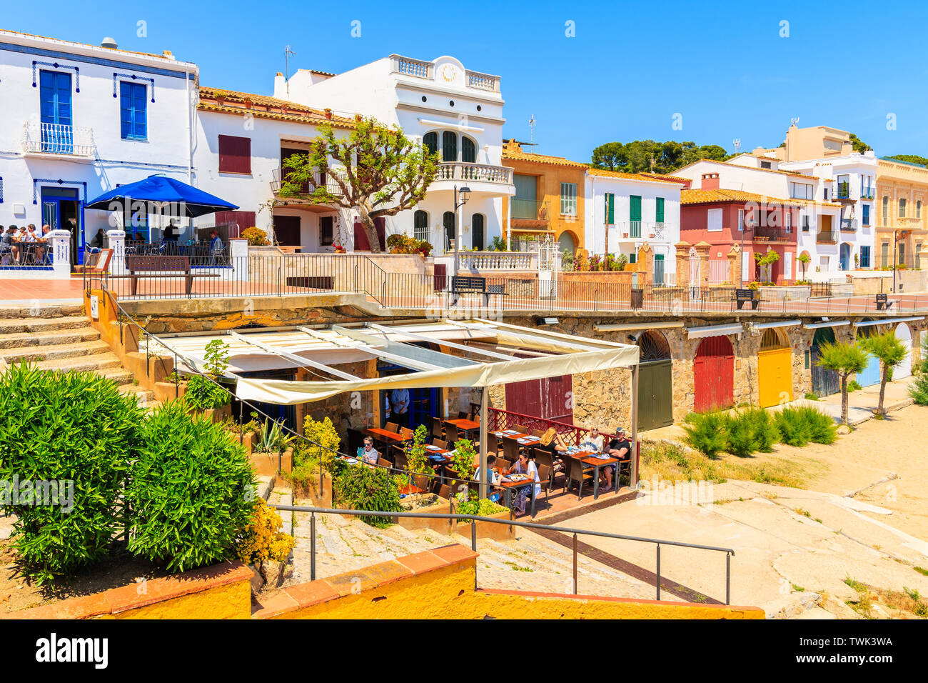CALELLA DE PALAFRUGELL, SPAIN - JUN 6, 2019: Restaurant on Canadell beach with colorful houses in backgrounf in Calella de Palafrugell village, Costa Stock Photo
