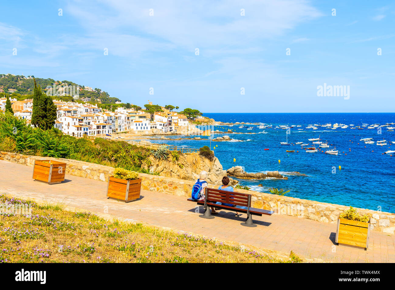Couple of tourists sitting on coastal promenade in Calella de Palafrugell, scenic fishing village with small castle and sandy beach with clear blue wa Stock Photo