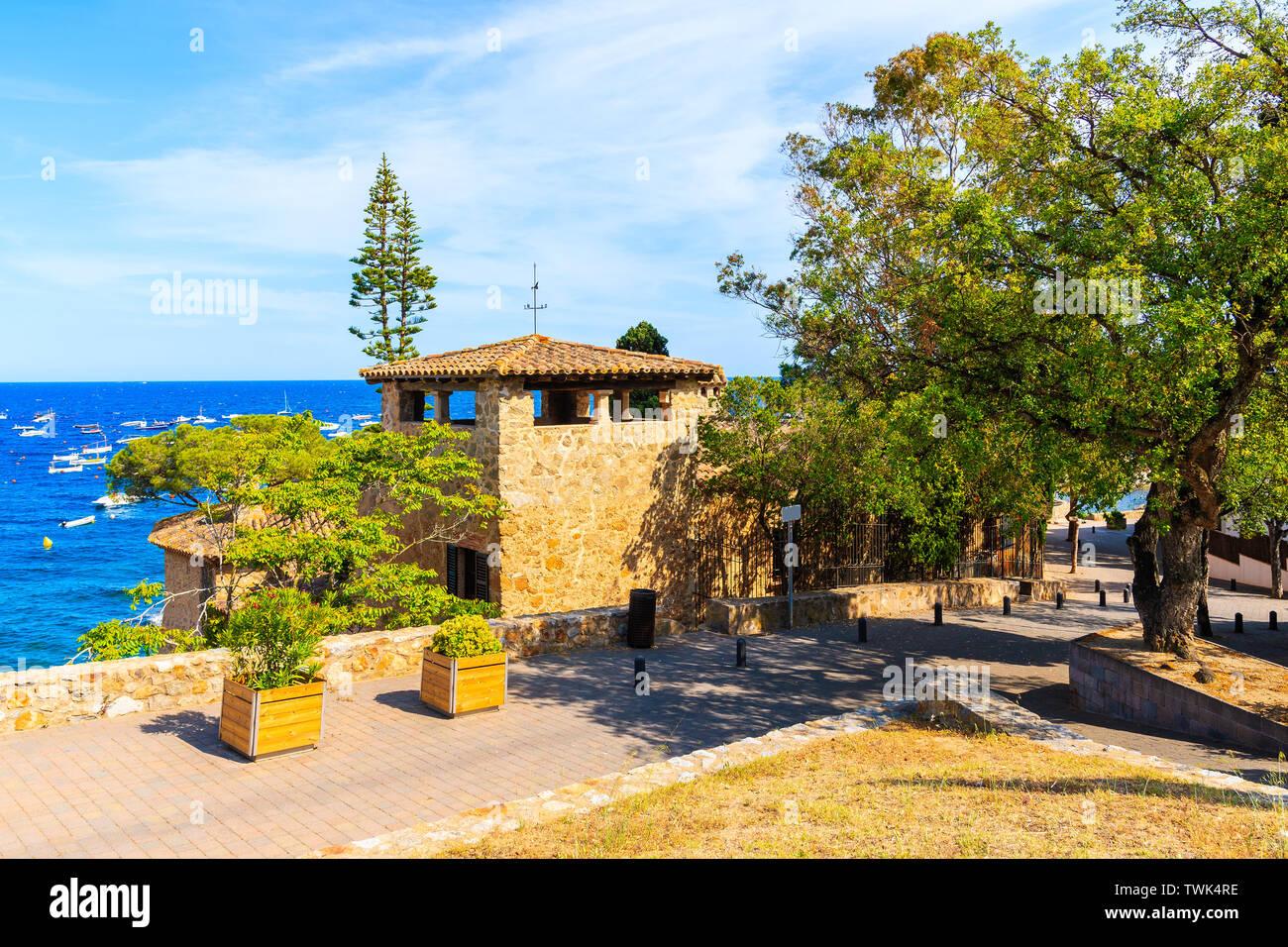 Coastal promenade in Calella de Palafrugell, scenic fishing village with small castle and sandy beach with clear blue water, Costa Brava, Catalonia, S Stock Photo