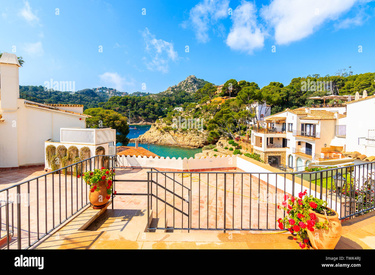 Terrace with flowerpots overlooking beach and holiday apartments in Fornells village, Costa Brava, Spain Stock Photo
