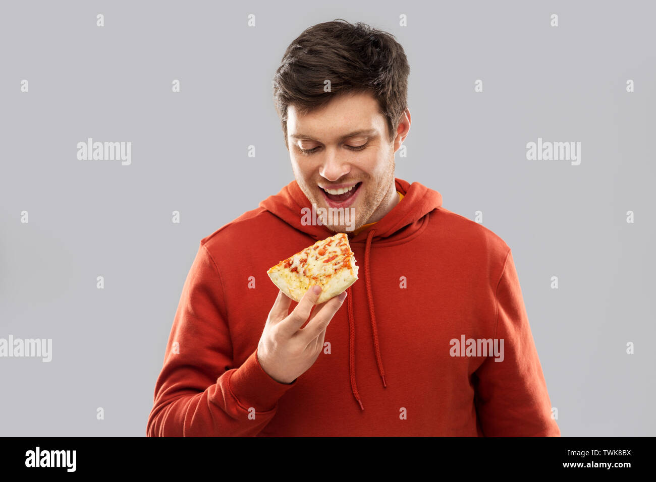 happy young man eating pizza - Stock Image