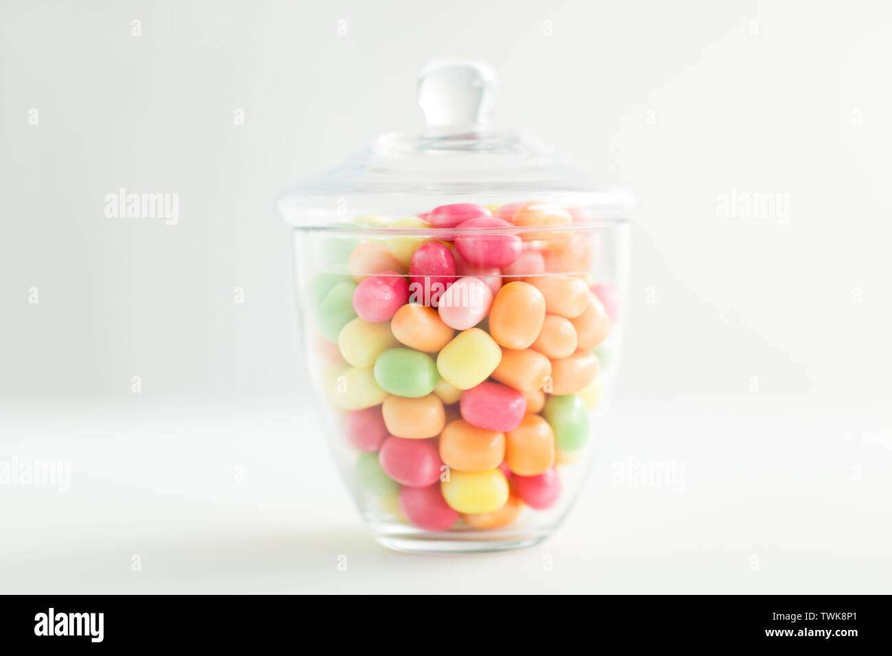 glass jar with candy drops over white background - Stock Image