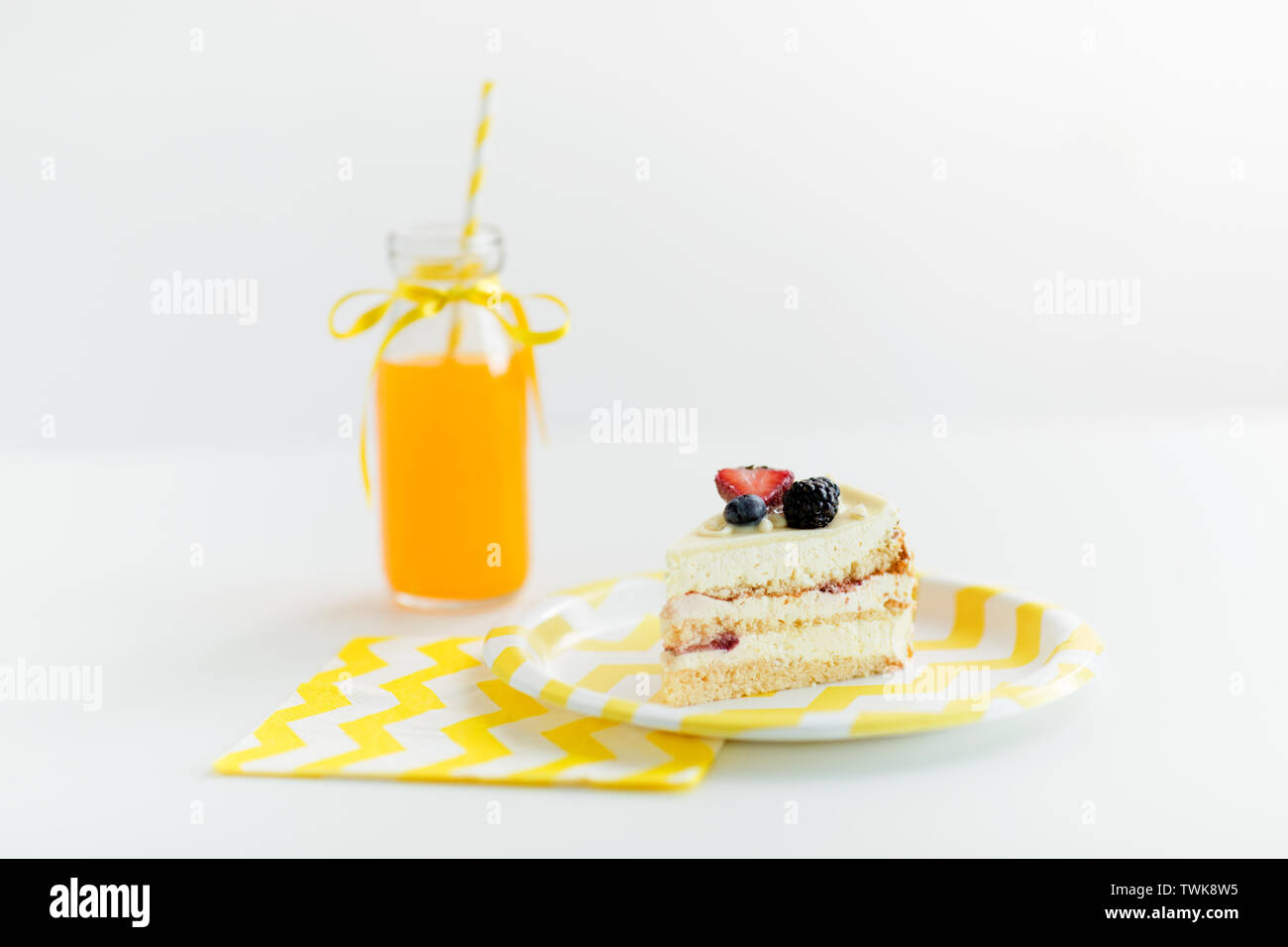 piece of berry layer cake on disposable plate - Stock Image