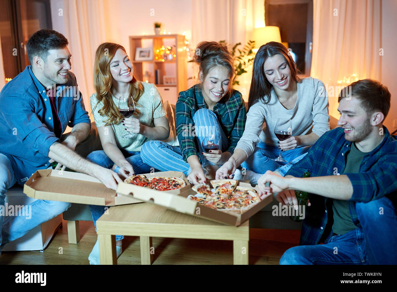 friends eating pizza and drinking red wine at home - Stock Image