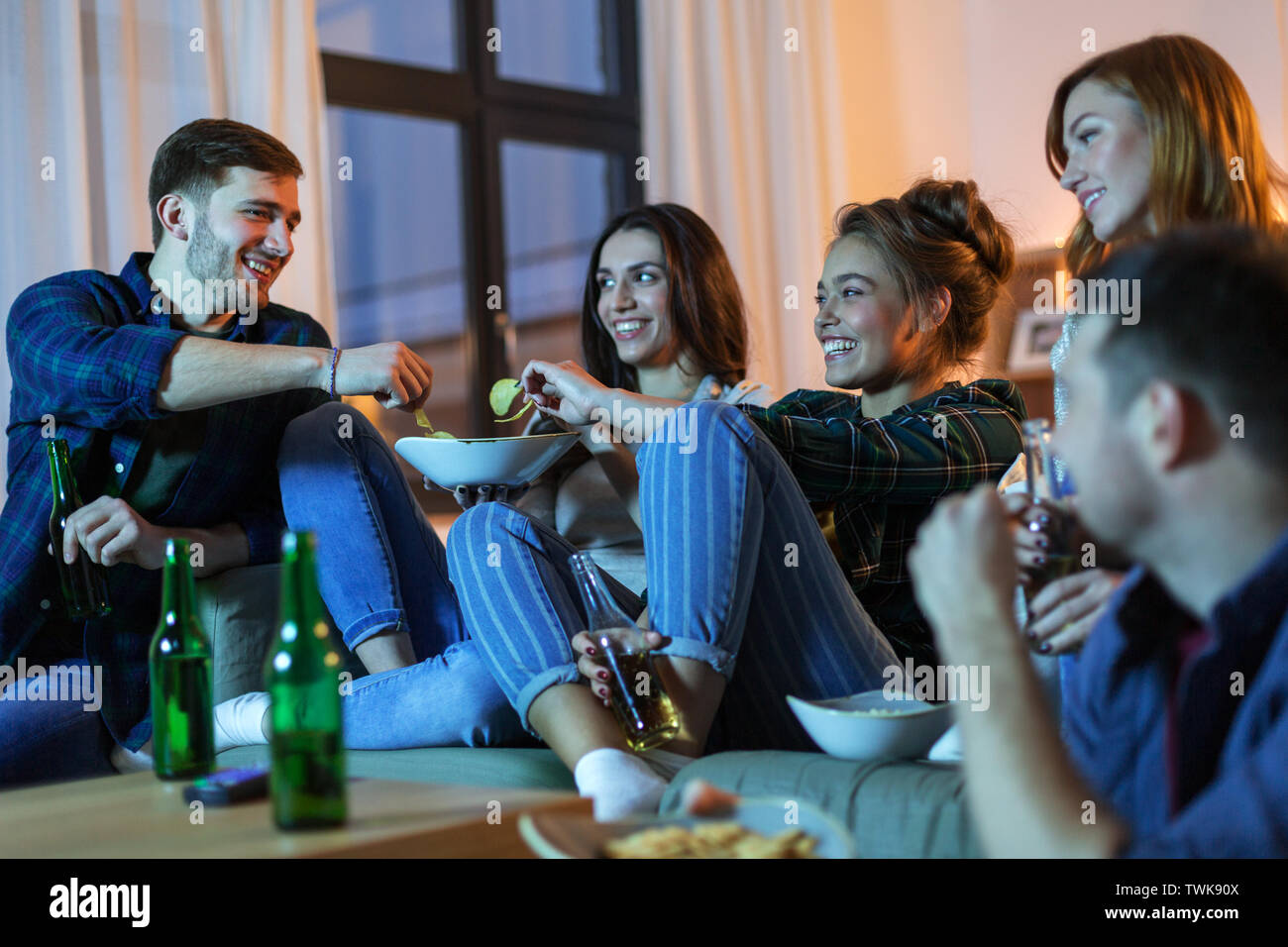 friends with drinks and snacks watching tv at home - Stock Image