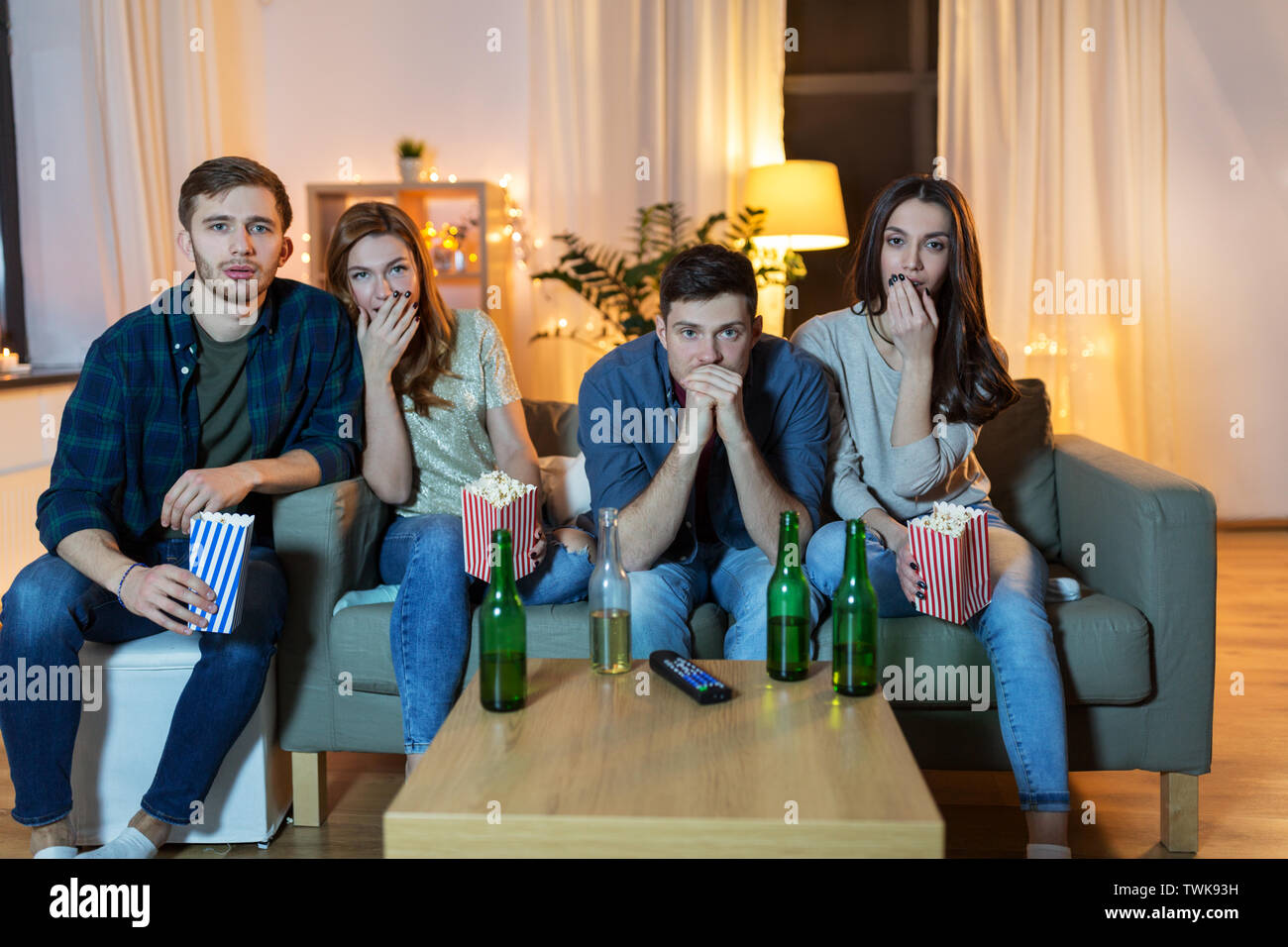 friends with beer and popcorn watching tv at home - Stock Image