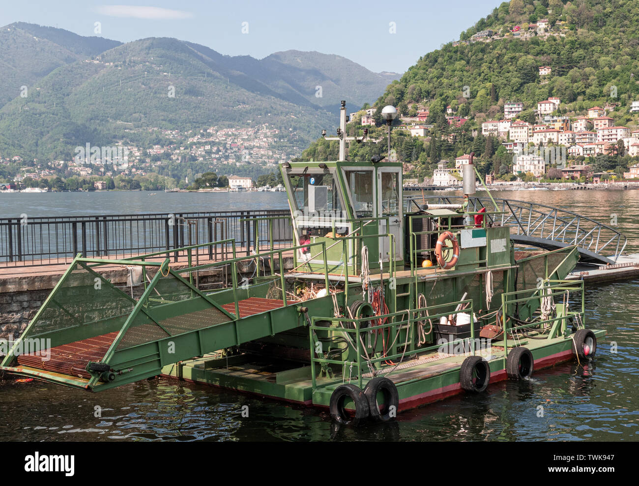 Como Lake - Italy. boat used for water cleaning and waste collection, moored in the port of Como - Stock Image