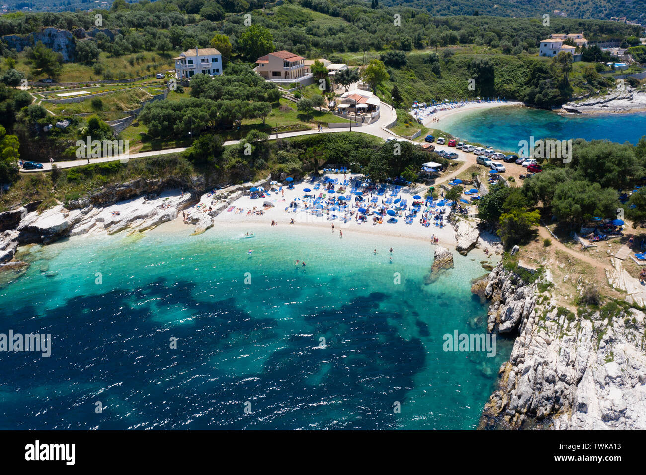 Aerial view of Cassiopi beach, holiday makers relaxing and swimming in blue warm sea. - Stock Image