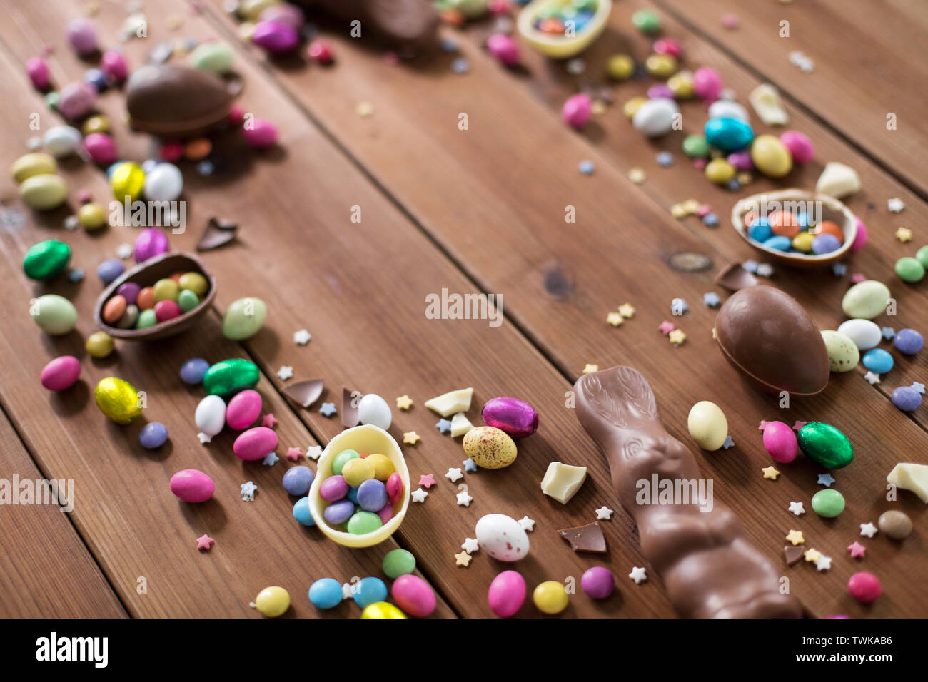 chocolate eggs and candy drops on wooden table - Stock Image