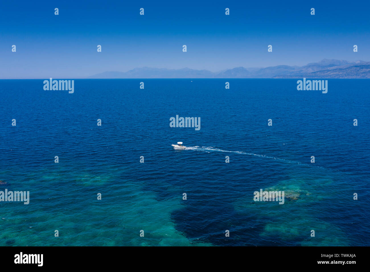 Aerial view of Cassiopi, beautiful deep blue sea with pleasure boat and mountains in the background. - Stock Image