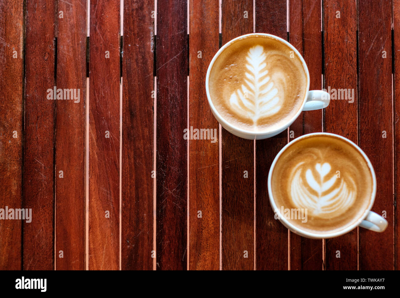 Two coffee cup leaf and heart shaped on wooden table - Stock Image