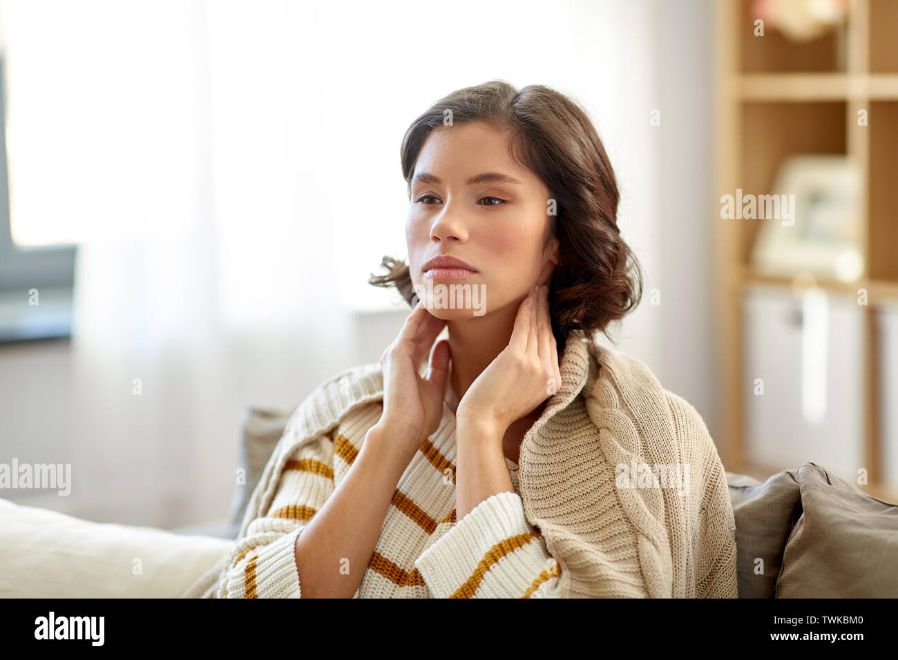 sick woman touching her lymph nodes at home - Stock Image