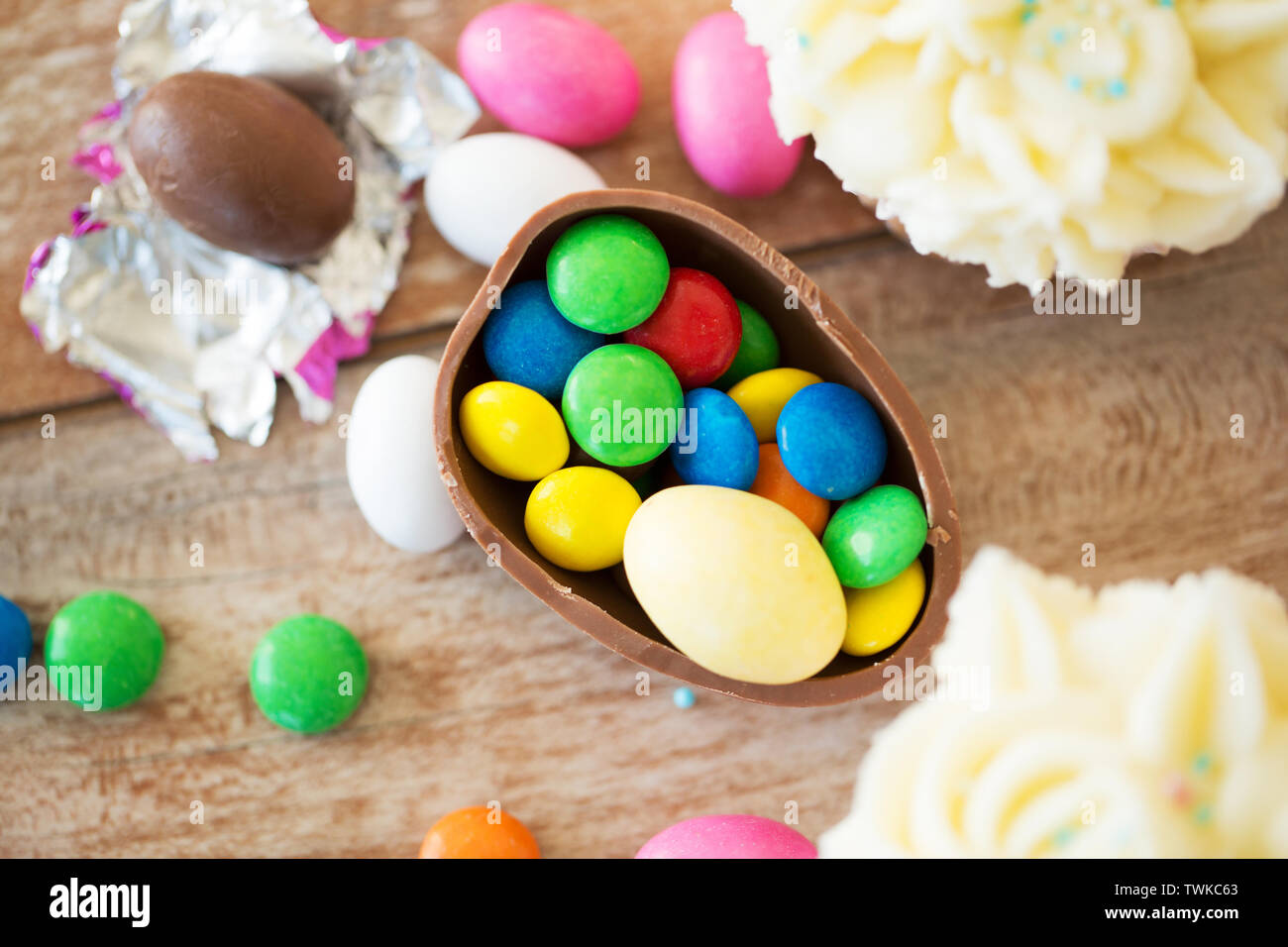 chocolate egg with candies and cupcakes on table - Stock Image