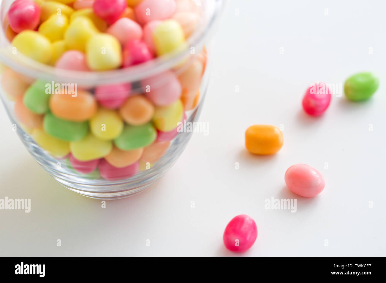 close up of glass jar with colorful candy drops - Stock Image