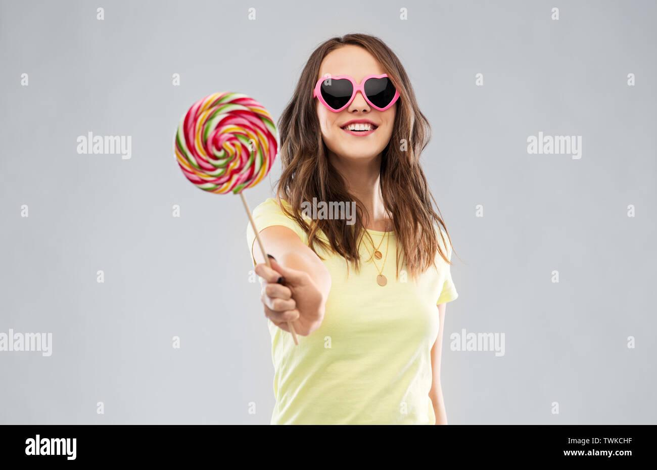 teenage girl in sunglasses with lollipop - Stock Image