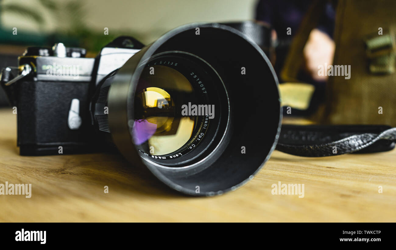 Old, vintage, retro style Spotmatic Pentax camera on wooden table - Stock Image