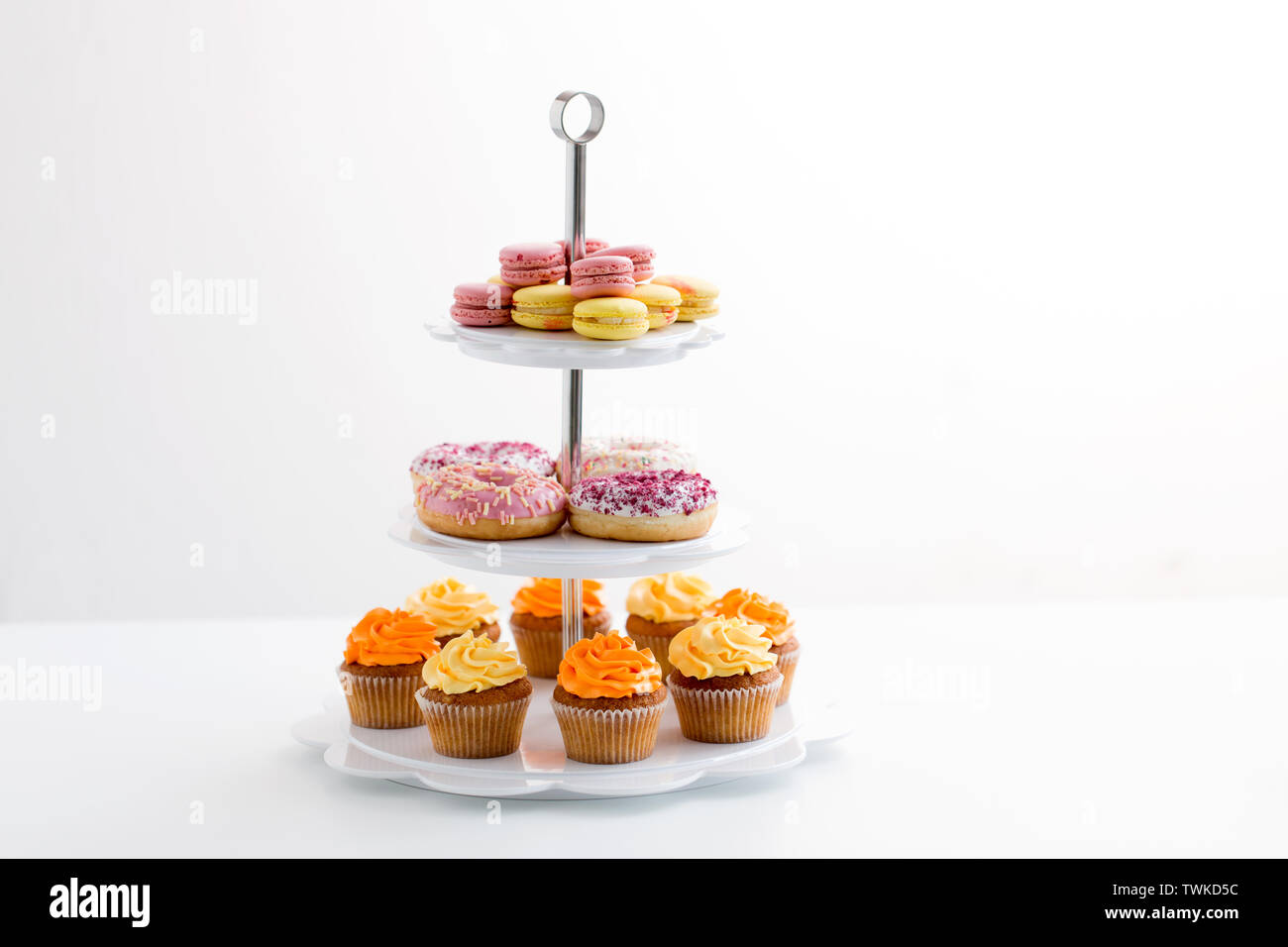 glazed donuts, cupcakes and macarons on stand - Stock Image
