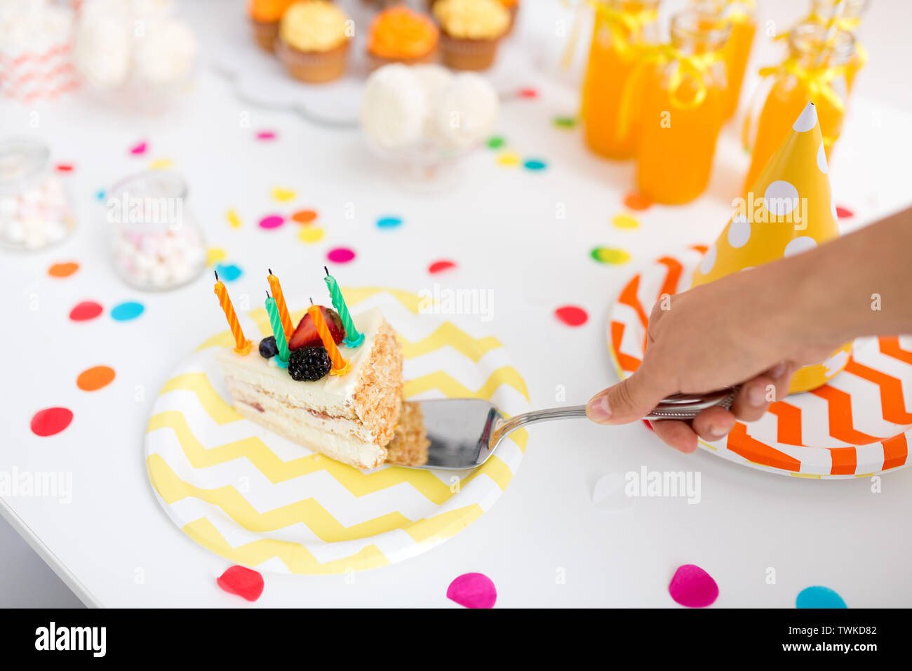hand putting piece of birthday cake on plate - Stock Image